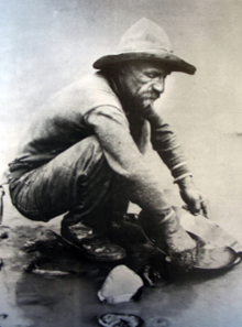 A gold prospector panning the precious metal using the gold pan.
