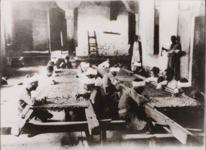 Photograph showing artisans at work at Dar al-Kiswah. 8.8 x 12 cm. Nasser D. Khalili Collection of Islamic Art © Nour Foundation. Courtesy of the Khalili Family Trust.