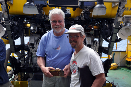 Recovery Limited Partnership's director of operations Craig Mullen (left) and chief scientist & historian Bob Evans (right) hold one of the five gold bars recovered by Odyssey's Remotely Operated Vehicle ZEUS (background) during the first reconnaissance dive to the SS Central America shipwreck in April 2014. Copyright: Odyssey Marine Exploration, Inc., www.OdysseyMarine.com.