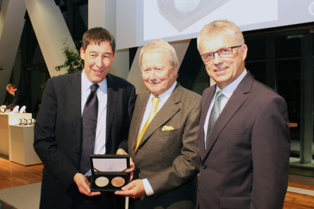 During the presentation Ralf Schumacher, Head of the Department for Finance and Economy, (left) gives the medal to Dr. Wolfgang Posche. On the right Peter Huber, Director of the State Mints of Baden-Wuerttemberg.