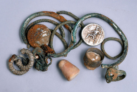A general picture of the cache of silver objects: two coins of Alexander of Macedon, three rings, four bracelets, two decorated earrings, three other earrings (probably made of silver) and a small stone weight. Photograph: Clara Amit. Courtesy of the Israel Antiquities Authority.