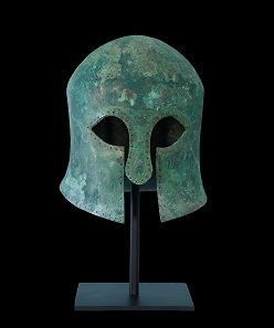 An ancient Greek bronze helmet of the Corinthian type, with curvilinear eye holes that taper to a point, a wide nose guard, broad cheek pieces that leave a vertical opening for the mouth, and a border that has been drilled with holes to secure an interior lining. Traces of the original crest are evident in the patina.