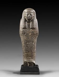 Lot 455: Tall ushabti. New Kingdom, ca. 1270-1080 BC. H 23 cm. Black basalt. From K.M. Collection, Thuringia. Estimate: 10,000,- euros. Hammer price: 20,000,- euros.