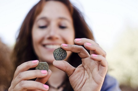Annette Landes-Nagar, director of the excavation, shows coins from the discovered hoard.
