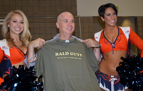 Accompanied by Denver Broncos cheerleaders Krista (left) and Brielle (right) the now-hairless Miles Standish holds a t-shirt proclaiming: BALD GUYS Never have a bad hair day. Photo credit: Donn Pearlman.