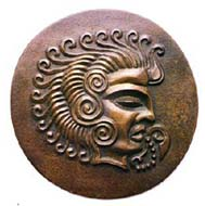 Coriosolite sun-god with wave-like curls of hair and sacred 'speech scroll' coming from mouth. Bronze medallion by Major N.V.L. Rybot. Source: A.L.T. McCammon, Currencies of the Anglo-Norman Isles, Spink 1984.